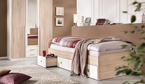 Einzelbett in hellem Holz-Look mit weißen Schubladen als Stauraum von mömax.