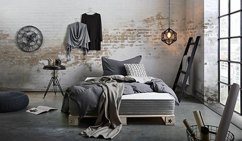 Palettenbett und dunkelgrau Boxspringmatratze von mömax, bunt mit Decken und Kissen dekoriert.