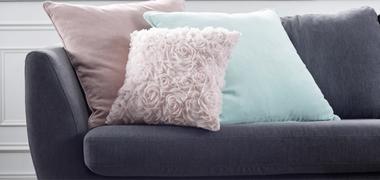 drei Heimtextilkissen auf einer Couch