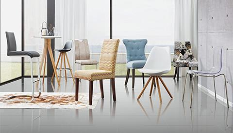 Eine Gruppe unterschiedlicher Sessel und Barhocker mit Bartisch von mömax, vor einer großen Fensterfront.