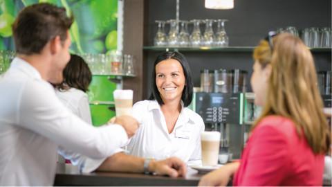 mehrere Menschen an einer Bar stoßen mit Milchkaffee an