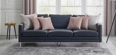dunkelgraue Couch mit verschiedenfarbigen Kissen auf grauem Boden
