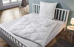 Weißes Rahmenbett mit Bettdecke und Kopfpolster, nicht bezogen, von mömax.