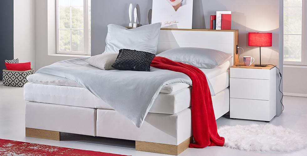Edles, weißes Lederlook-Boxspringbett mit Eichenholzfüßen, inklusive Strom- und USB-Anschlüssen von mömax.