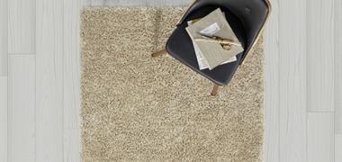 Teppich in beige mit einem schwarzen Sessel von oben