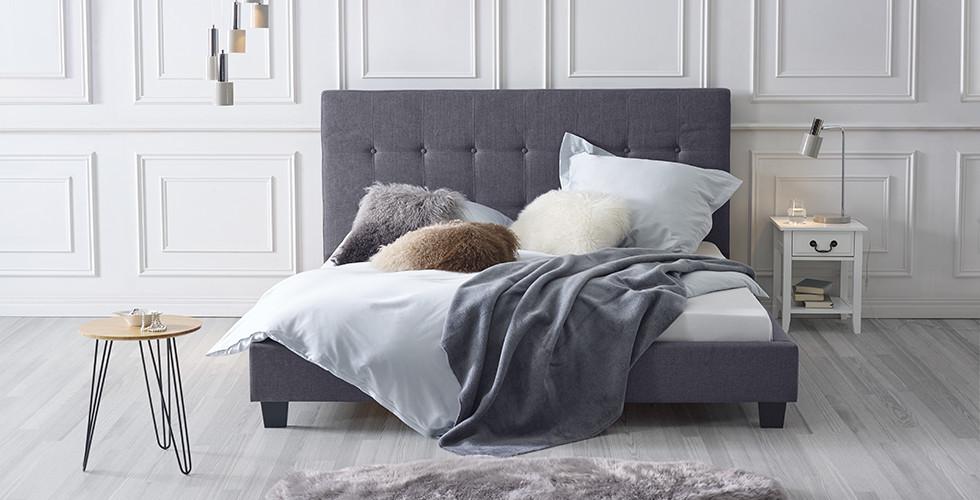 Bett mit hohem Kopfteil in Dunkelgrau, daneben ein Nachttisch mit Henkelgriff aus Metall, in Weiß, von mömax.