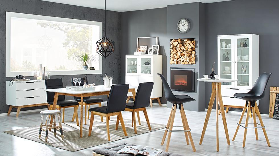 Esstisch mit weißer Tischplatte und Beinen in Walnussholz, dazu Sessel mit schwarzem Textilbezug, in einem großen Wohnraum mit hellem Boden und anthrazitfarbenen Wänden.