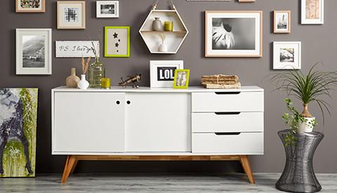 Weißes Sideboard mit zwei Schiebetüren und drei Schubladen, dekoriert, vor anthrazitfarbener Wand, von mömax.