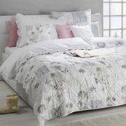 Bett mit Tagesdecke in grau weiß