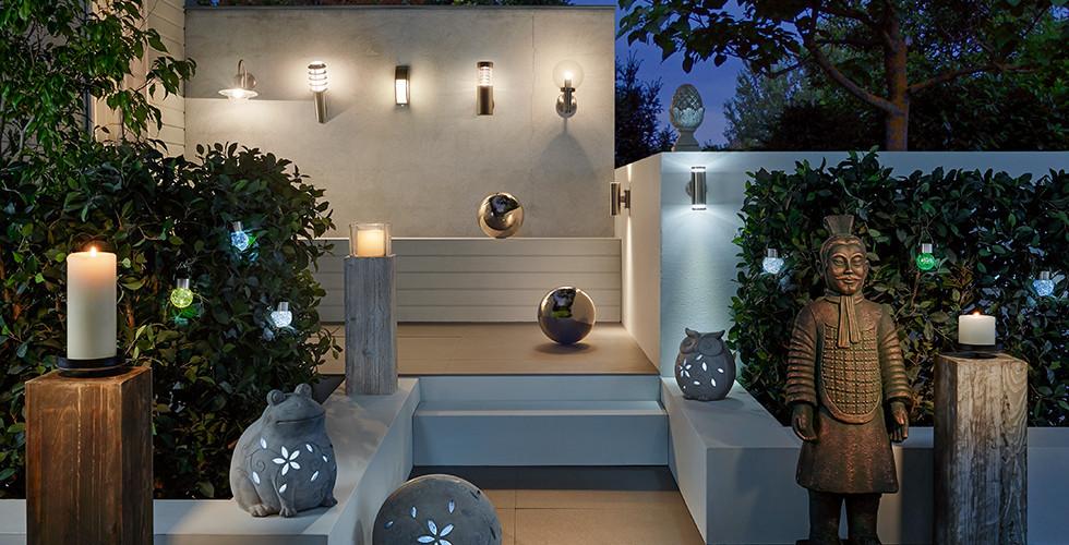 Terrasse mit Wandaußenleuchten in Stab- und Kugelform sowie Dekoleuchten in Tierform von mömax.