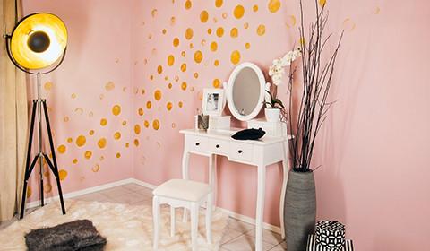 Goldene Punkte auf eine rosafarbene Wand gestempelt.