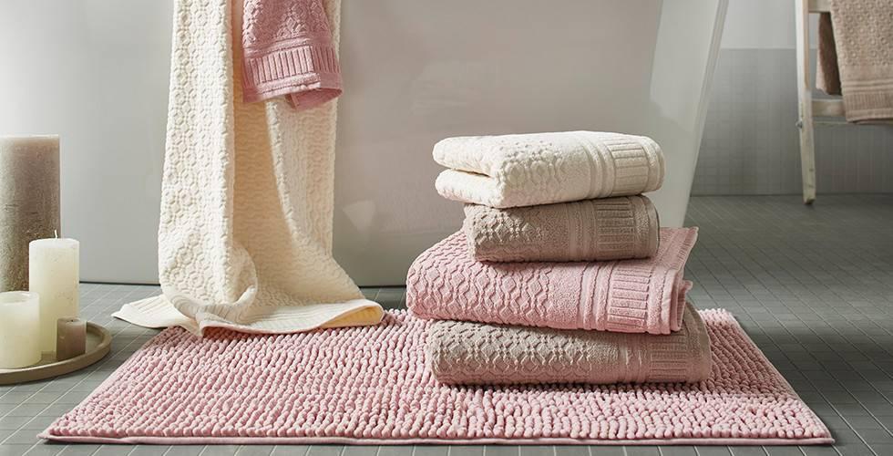 Gestapelte Handtücher in Beige, Rosa und Weiß, auf einer rosafarbenen Badematte, von mömax.