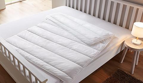 Gesteppte Bettdecke, auf einem Bett mit weißem Leintuch liegend, von mömax.