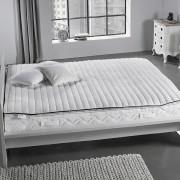 Matratzentopper auf einem Bett in einem grau gehaltenen Raum