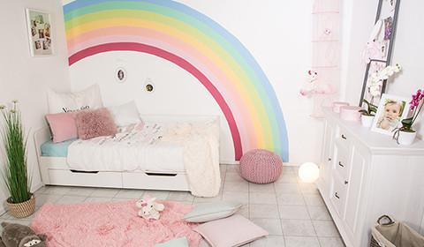 Wandgestaltung mit buntem Regenbogen im Kinderzimmer.