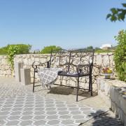 schwarze Gartenbank vor einer halbhohen Steinmauer