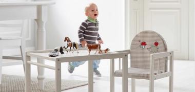 Babyzubehör, Spielsachen auf einem Babytisch mit Stuhl in weiß