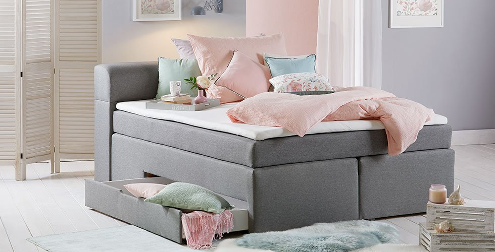 Udobna boxspring postelja antracitne barve z dodatnim predalom in posteljnino roza barve