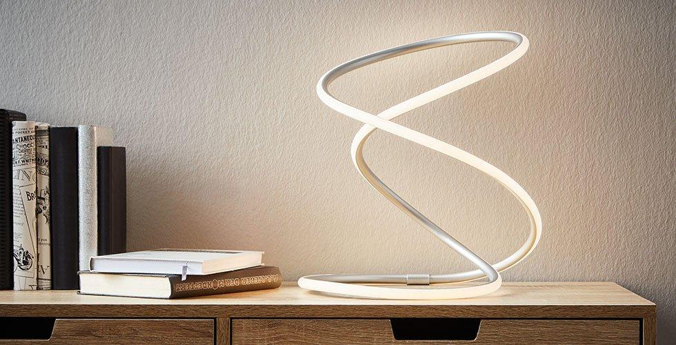 Trendig geschwungene LED-Tischleuchten aus Aluminium und Silikon von mömax.