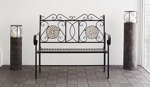 Attraktive Gartenbank aus Metall in Schwarz und dekorativen Mosaiken in Weiß im Bereich der Rückenlehne.