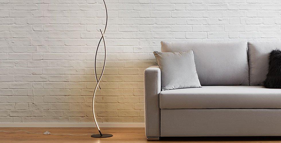 Moderne LED-Stehleuchten mit geschwungener LED-Lichtleiste und rundem Standfuß von mömax.