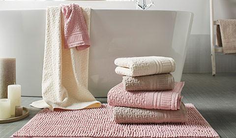 Handtücher in Weiß, Beige und Rosa, gestapelt auf einer rosafarbenen Badematte, von mömax.
