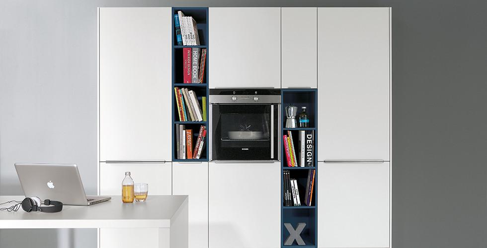 Wohnküche in kühlem Weiß mit integriertem Backofen und Bücherregalen von mömax.