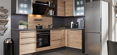 Eckküche mit Kühlschrank mit anthrazitfarbener Arbeitsplatte und holzfarbenen Fronten