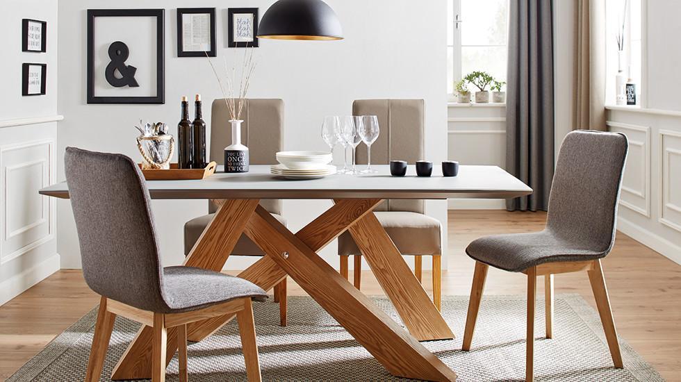 Esstisch mit x-förmigen Beinen in Eiche, dazu passende Sessel mit grauem Textilbezug, von mömax