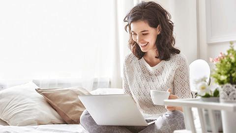 braunhaarige Frau im Bett mit Kaffee schaut in Laptop