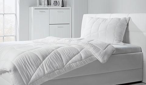 Gesteppte Bettdecke und gestepptes Kopfkissen auf weißem Bett, von mömax.