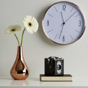 Wanduhr mit Blumenvase und Kamera im Vordergund