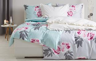 Doppelbett und Bettwäsche mit Blumenmuster von mömax.