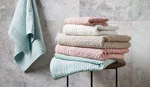 Gestapelte Handtücher in Creme, Taupe, Rosa und Mintgrün von mömax.