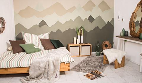 Wandgestaltung mit gemaltem Bergpanorama.