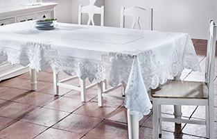 Esstisch mit weißer Tischdecke und drei Stühlen, von mömax.