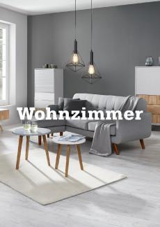 graue Couch mit Decke und runden Beistelltischen davor